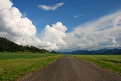 Forward. Country road, beautiful landscape, asphalt, way forward, cloudy sky, Altai, Russia, blue sky and white clouds, outdoor, moving Royalty Free Stock Images
