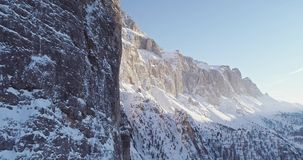 Forward aerial along snowy alpine steep rocky cliff valley.Sunny day,clear sky.Winter Dolomites Italian Alps mountains. Outdoor nature establisher.4k drone stock video footage