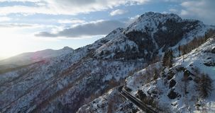 Forward aerial top view over car travelling on road in Winter snow mountain near forest woods.Snowy mountains street. Path establisher.Sunset or sunrise sun stock footage