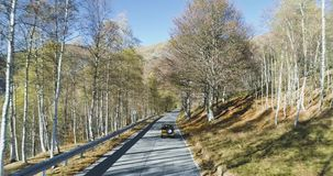 Forward aerial top view over yellow vintage car travelling on road in colorful autumn forest.Fall orange,green,yellow. Forward aerial top view over car stock video footage