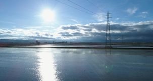 Forward aerial view flooded rice agricultural rural fields with electric line pylon. Daylight sunny summer or spring stock video footage