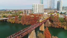 Forward aerial view of train on Bridge in Austin Texas. Austin, TX - Circa December, 2017 - A slow forward aerial view of a train traveling on a bridge over the stock video footage