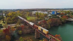 Forward aerial view of train on Trestle Bridge in Austin Texas. Austin, TX - Circa December, 2017 - A slow forward aerial view of a cargo train traveling over a stock footage