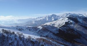 Forward aerial on white snow mountain peak in winter revealing valley.Forest woods.Snowy mountains establisher with. Backlit sun.Italian Alps.4k drone flight stock footage