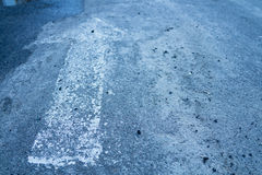 Forward arrow on the asphalt. White arrow forward on dark asphalt. The symbol is located on the left in the picture Royalty Free Stock Photos