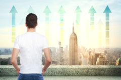 Forward concept. Back view of young businessman on rooftop looking at New York city with upward chart arrows. Forward concept Stock Images