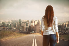 Forward concept. Back view of young woman on road looking at moden city. Forward concept Stock Photos