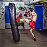 Forward kick. Muay Thai fighter giving a forceful forward kick during a practice round with a boxing bag Stock Image