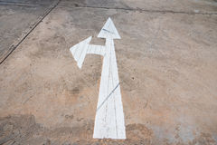 Forward and left arrow sign on paved road, Arrow on the road poi. Nting in two directions royalty free stock images