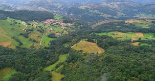 Forward movement of an aerial view with forests, fields and a village