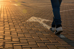 Free Forward Movement. Feet On The Road With Arrows In The Rays Of The Setting Sun Stock Photo - 89606860