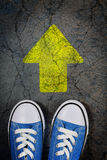 Forward. Sneakers on cracked concrete surface with painted arrow Royalty Free Stock Photography