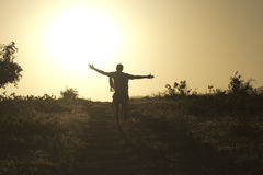 Forward to the light!. Man runs straight to the setting sun Stock Image