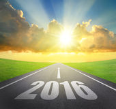 Forward to 2016 new year concept. Asphalt road with arrow , date and beautiful sunset and sunshine Royalty Free Stock Images