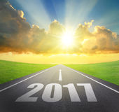 Forward to 2017 new year concept. Asphalt road with arrow , date and beautiful sunset and sunshine Royalty Free Stock Image