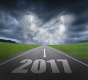 Forward to 2017 new year concept. Danger to 2017 new year concept , rainstorm clouds and lightning with asphalt road Stock Image