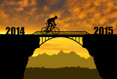 Forward to the New Year 2015. Cyclist riding across the bridge at sunset .Forward to the New Year 2015 Stock Photo