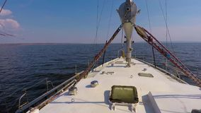 Forward view from the deck white steel yachts going under the motor on dark blue water under a blue sky without clouds. View forward from the deck white steel stock video footage