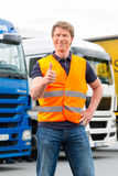 Forwarder or driver in front of trucks in depot royalty free stock photography