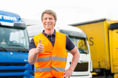 Forwarder or driver in front of trucks in depot. Logistics - proud driver or forwarder in front of trucks and trailers, on a transshipment point stock photo