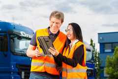 Forwarder in front of trucks on a depot. Logistics - proud driver or forwarder and female coworker with tablet computer, in front of trucks and trailers, on a royalty free stock photo