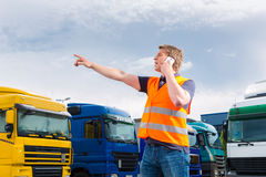 Forwarder in front of trucks on a depot. Logistics - proud driver or forwarder with mobile phone in front of trucks and trailers, on a transshipment point royalty free stock image