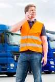 Forwarder in front of trucks on a depot. Logistics - proud driver or forwarder with mobile phone in front of trucks and trailers, on a transshipment point stock image