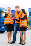 Forwarder in front of trucks on a depot. Logistics - proud driver or forwarder and colleagues with tablet computer, in front of trucks and trailers, on a stock images