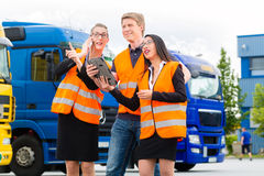 Forwarder in front of trucks on a depot. Logistics - proud driver or forwarder and colleagues with tablet computer, in front of trucks and trailers, on a stock photo