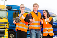 Forwarder in front of trucks on a depot. Logistics - proud driver or forwarder and colleagues with tablet computer, in front of trucks and trailers, on a royalty free stock photo