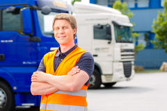 Forwarder in front of trucks on a depot. Logistics - proud driver or forwarder in front of trucks and trailers, on a transshipment point royalty free stock images