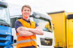 Forwarder lub kierowca przed ciężarówkami w zajezdni Fotografia Stock