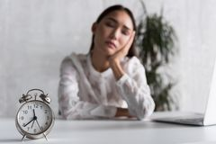 Forworn female person falling asleep near workplace. Tired of work. Exhausted woman is sitting at desk and sleeping. Focus on alarm clock. Copy space on right Royalty Free Stock Images