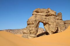 Forzhaga Arch and sand dunes. Forzhaga natural rock arch surrounded by sand dunes, Akakus Acacus Mountains, Sahara Desert, Libya Stock Photography