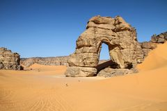 Forzhaga Arch and sand dunes. Forzhaga natural rock arch surrounded by sand dunes, Akakus Acacus Mountains, Sahara Desert, Libya Stock Images
