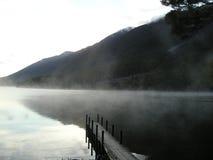 Foschia calma di mattina sul lago Fotografia Stock
