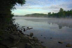 Foschia che aumenta da un lago nella regione selvaggia Immagine Stock