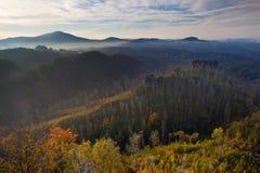 Foschia di mattina nel paesaggio roccioso con le colline e le foreste alla caduta Immagine Stock