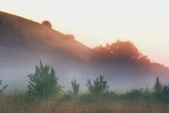 Foschia di mattina sopra i prati ed i campi vicino alle colline Immagini Stock