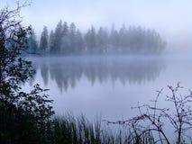 Foschia di mattina su un lago della montagna. Fotografie Stock