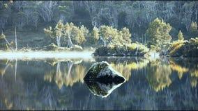 Foschia di mattina sul lago calmo con roccia video d archivio