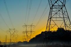 Foschia e powerlines di mattina Immagini Stock
