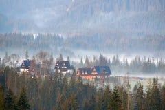 Foschia nebbiosa di mattina sopra la valle della montagna con le costruzioni di casa rurali di legno dell'azienda agricola Immagini Stock