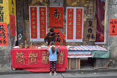 FOSHAN, CHINA - CIRCA ENERO DE 2019: Un viejo hombre que escribe bendiciendo pareados imagen de archivo
