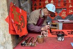 FOSHAN, CHINA - CIRCA FEBRUARI 2018: Een oude mens die zegenend coupletten bij de gelegenheid van de Lentefestival schrijven De b Stock Foto's