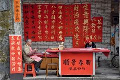 FOSHAN, CHINA - CIRCA FEBRUARY 2018: A calligrapher´s stand. A calligrapher´s stand where an old couple takes a rest. The meaning of the characters are royalty free stock photos
