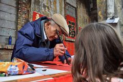 FOSHAN, CHINA - CIRCA JANUARY 2018: An old man writing blessing antithetical couples during the Spring Festival. A translation of a character in the background stock photos