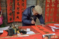 FOSHAN, CHINA - CIRCA JANUARY 2018: An old man writing blessing antithetical couples during the Spring Festival. A translation of. An old man writing blessing stock photos