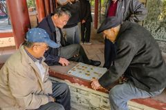 Senior Chinese People let relax and playing Chinese Chess in The Ancestral temple park.Foshan city china stock photos