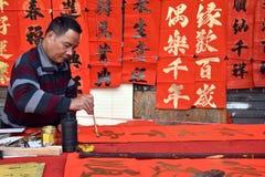 FOSHAN, CHINY - OKOŁO STYCZEŃ 2019: Stary człowiek pisze błogosławieństwo przyśpiewkach przy okazją wiosna festiwal obraz royalty free